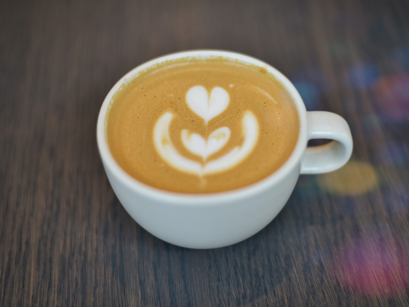 A fresh cup of coffee from a cafe made by barista