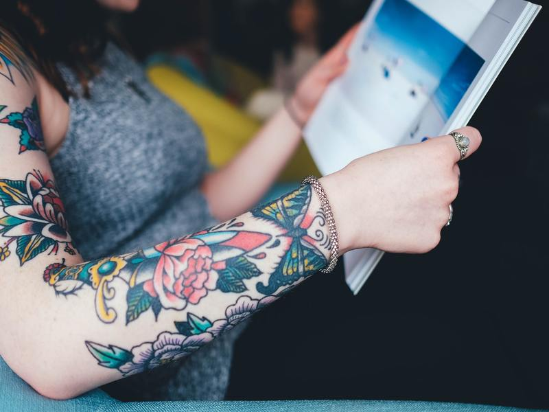 lady reading a magazine with colorful sleeve tattoo showing a red flower, yellow and green butterfly