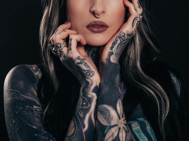 Lady with hands to face showing off full arm tattoos and written words