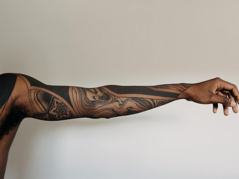 White background with an arm showing black tribal tattoos
